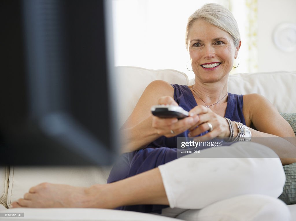 Senior woman watching television, smiling : Stock Photo