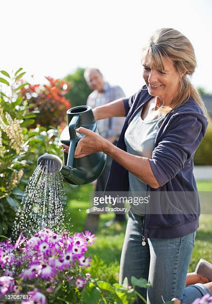 Senior woman watering flowers in garden with watering can