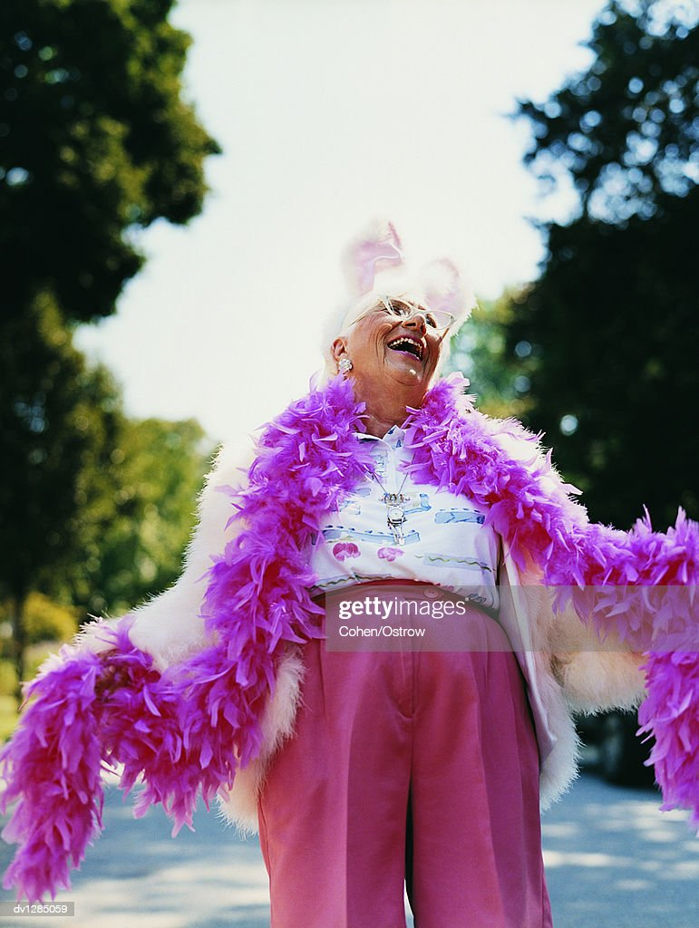 Senior Woman Wearing a Feather Boa and a Rabbit Costume Laughing and Looking Upwards : Stock Photo