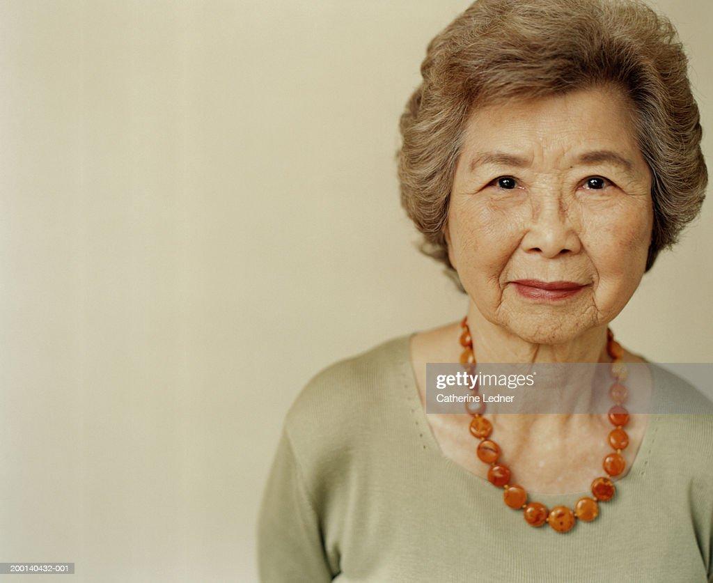 Senior woman wearing amber necklace, portrait : Stock Photo