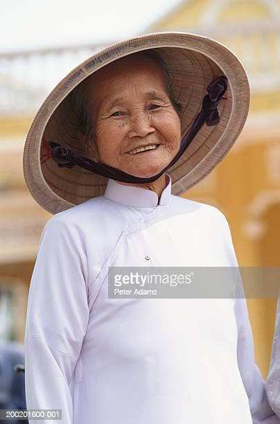 Senior woman wearing Cao Dai robes, smiling, close-up, portrait