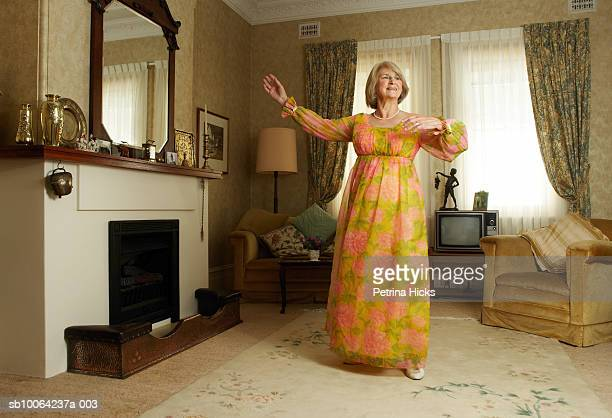 Senior woman wearing dress dancing in living room