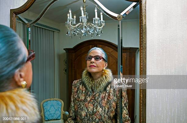 Senior woman wearing fur collared coat, looking in mirror