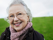 Senior Woman wearing glasses and smiling to camera