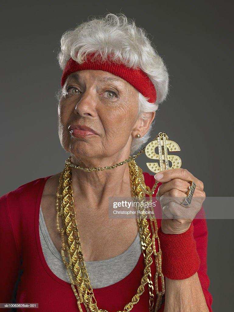Senior woman wearing gold chains, holding dollar symbol : Stock Photo