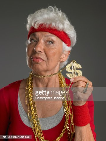 Senior woman wearing gold chains, holding dollar symbol