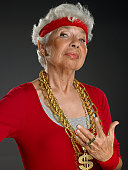 Senior woman wearing gold chains with dollar symbol, portrait