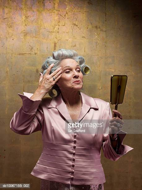 Senior woman wearing hair curlers looking in hand mirror, studio shot