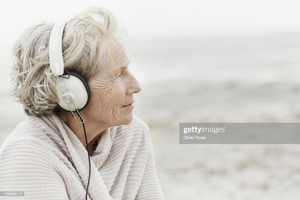 Senior woman wearing headphones on the beach : Stock Photo