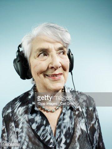A senior woman wearing headphones
