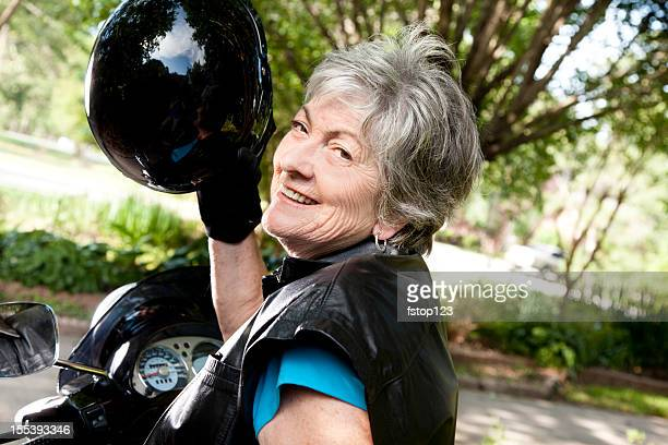 Senior woman wearing helmet, leather vest and gloves riding motorbike
