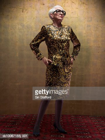 Senior woman wearing leopard print dress standing in studio