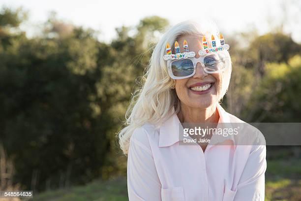 Senior woman wearing party glasses, Hahn Park, Los Angeles, California, USA