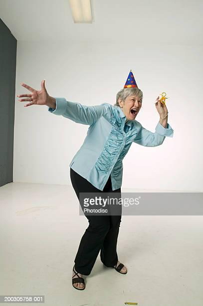 Senior woman wearing party hat, dancing in studio, portrait