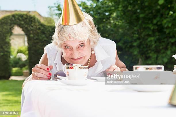 Senior woman wearing party hat looking at camera, smiling