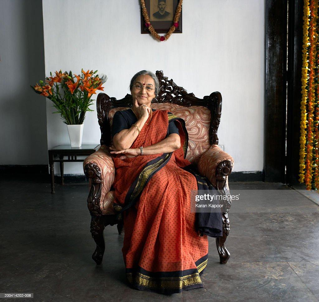 Senior woman wearing sari sitting in armchair smiling, portrait