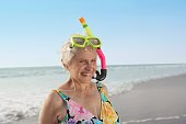 Senior woman wearing snorkeling gear on the beach