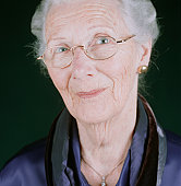Senior woman wearing spectacles smiling, posing in studio, portrait