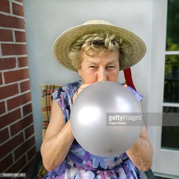 Senior woman wearing straw hat, blowing balloon