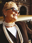 Senior woman wearing sunglasses and pearl necklace, smiling, close-up