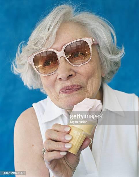 Senior woman wearing sunglasses, holding ice cream cone, close-up