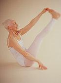 Senior woman wearing white leotard performing gymnastics on floor