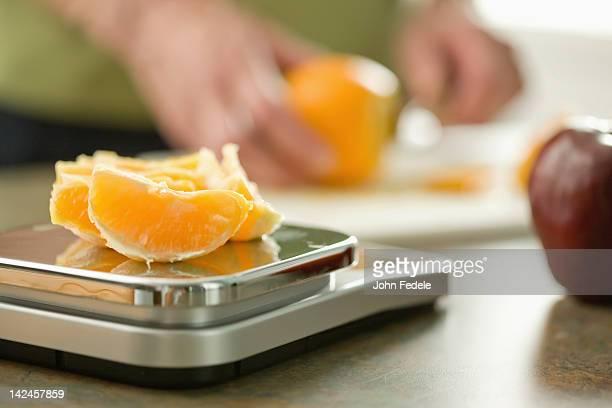 Femme Senior sur échelle pesant orange