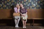Senior woman whispering to friend