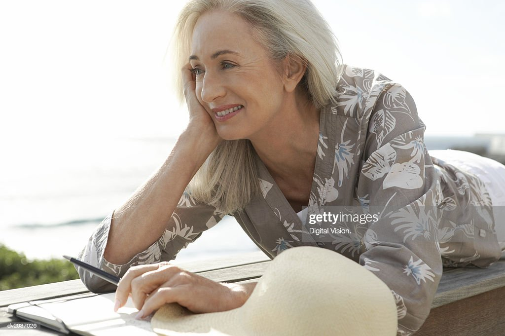 Senior Woman With a Notepad and Pen Lying on Wooden Decking by the Coast With Her Hand on Her Chin : Stock Photo