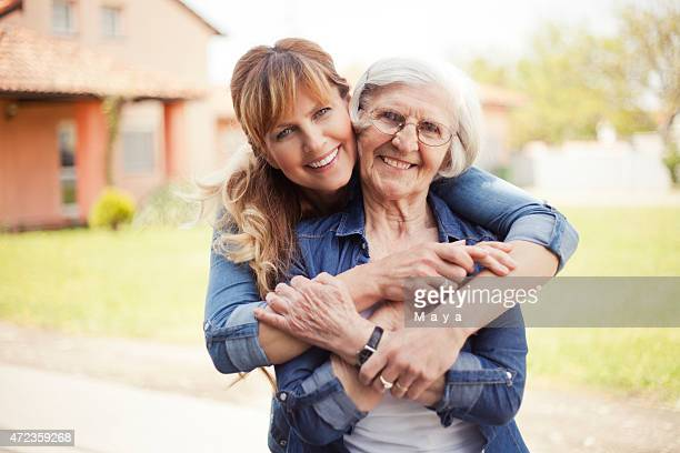 Senior woman with adult daughter hugging her from behind