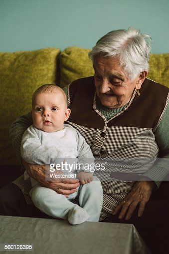 Senior woman with baby boy on her lap at home