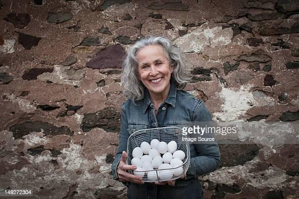 年配の女性、バスケットの卵