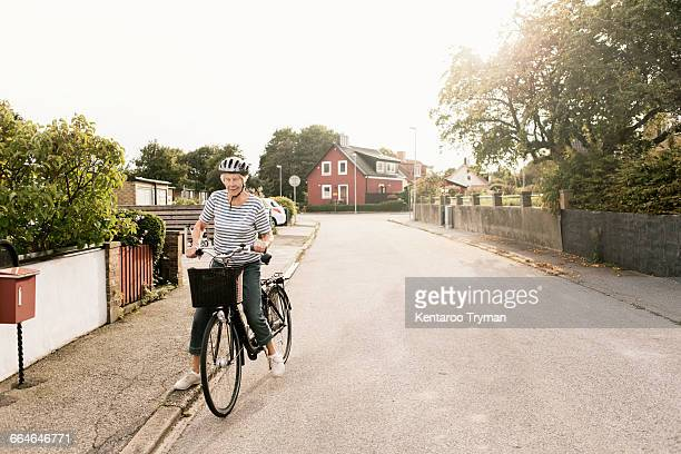 Senior woman with bicycle on road against house