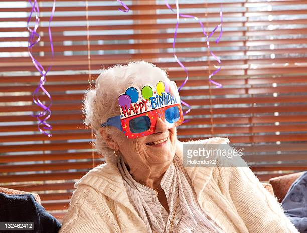 Senior woman with birthday glasses on