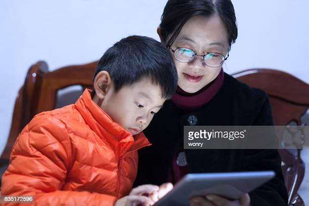 Senior woman with boy using digital tablet