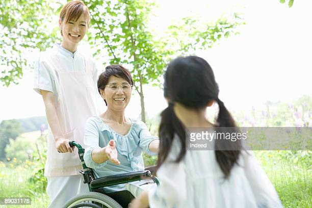 Senior woman with care giver smiling to girl
