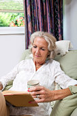 Senior woman with coffee cup reading book while relaxing on armchair at home