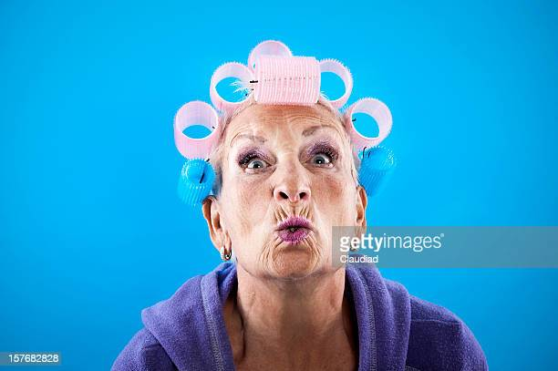 Senior woman with curlers is kissing