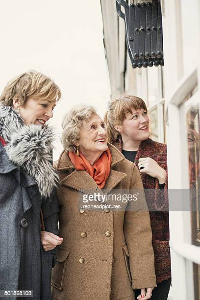 Senior woman with daughter and granddaughter, looking in window