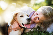 Unrecognizable senior woman with a dog lying down on a grass outside in spring nature, resting.