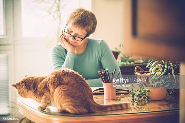 Mulher idosa com óculos Livro de Colorir em casa, a Europa
