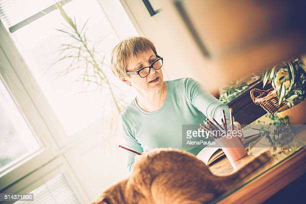 Senior Woman with Eyeglasses Coloring Book at Home, Europe