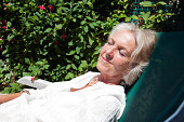 Senior woman with eyes closed relaxing on lounge chair in garden