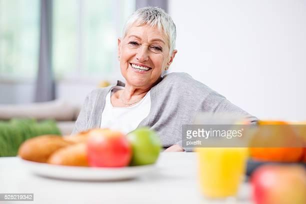 年配の女性、フルーツとオレンジジュース