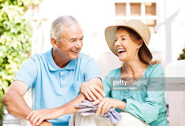 Senior Woman With Gardening Gloves Laughing While Sitting By Man