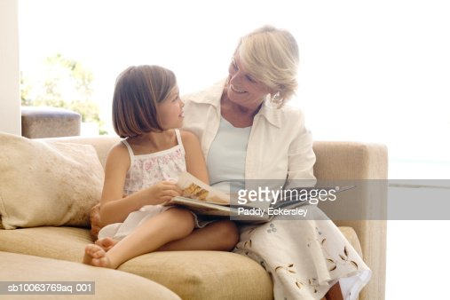 Senior woman with granddaughter (8-9) sitting on sofa, reading book : Foto stock
