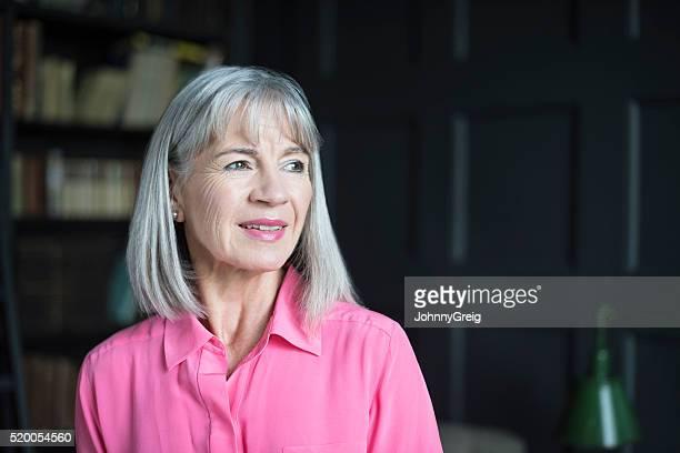 Senior Frau mit grauem Bob Wegsehen Lächeln