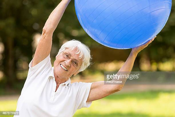 Senior woman with gymnastics ball in the park