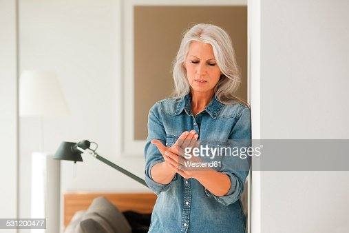 Senior woman with hand pain standing in living room