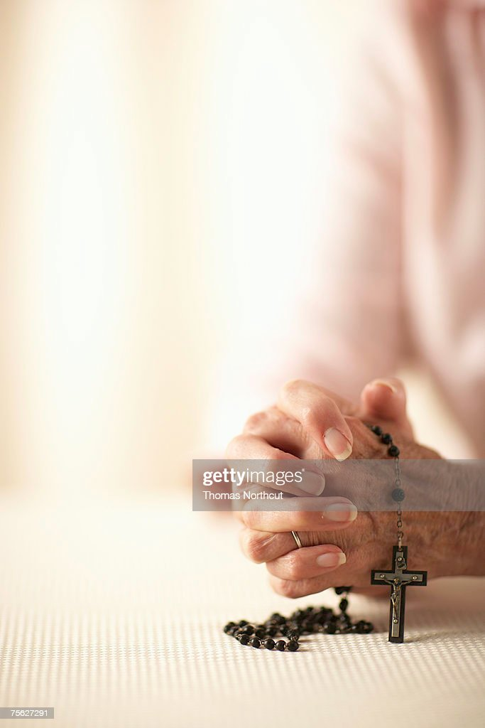 Senior woman with hands clasped, holding rosary, mid section, close-up of hands